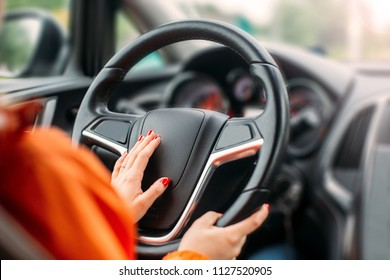 Young woman driver driving a business car.