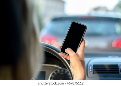 Young woman driver reading a text message on her mobile while driving her car in traffic, close up view on her hand and phone with a view through the windscreen