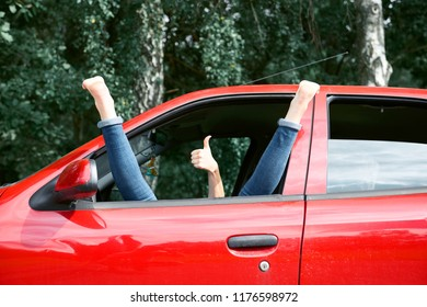 young woman driver resting in a red car, put her feet on the car window and gesturing, happy travel concept