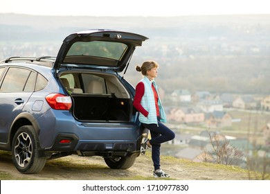 Young woman driver standing alone near her car enjoying view of nature landscape.