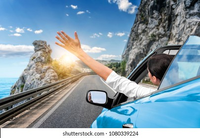 Young woman is driving by car to the sea and waving her hand from a blue convertible car. Vacation on the sea coast.