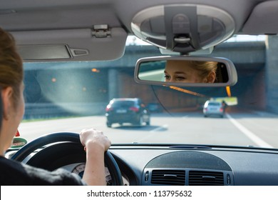 Young woman driving by car on the autobahn, view from inside the auto