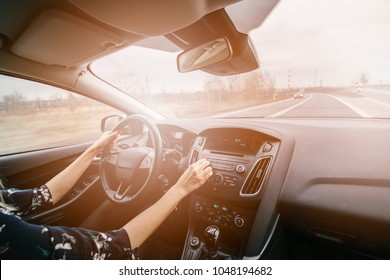 Young woman driving a car and adjusting car audio. Music in a car. Sunny day. Modern car interior