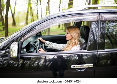Young woman driving a car in the city. Portrait of a beautiful woman in a car. Travel and vacations concepts