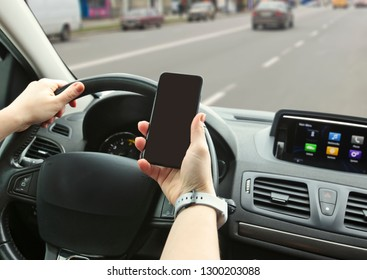 Young woman driving the car and looking on her phone