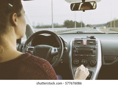 Young woman driving car on highway. Driver's perspective holding steering wheel.