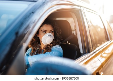 Young woman driving car with protective mask on her face.  Healthcare, virus protection, allergy protection concept.