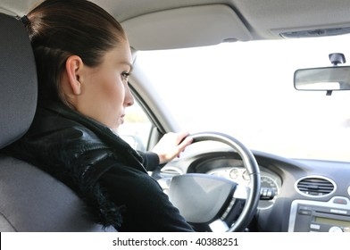 Young woman driving car - rear view on person and window