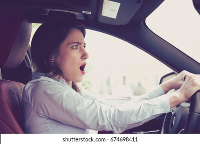 Young woman driving a car shocked about to have traffic accident, side window view