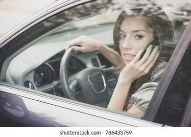 Young woman driving a car while talking on the mobile phone