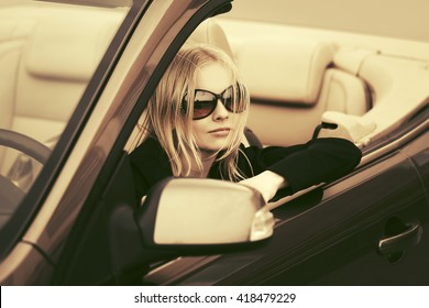 Young woman driving convertible car. Female fashion model in sunglasses outdoor