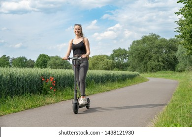 Young woman driving with electric scooter on bike path