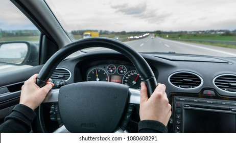 Young woman driving fast fast car on motorway