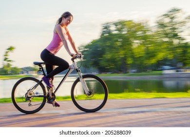 young woman driving on bicycle in evening park
