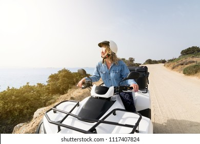 Young woman driving rental ATV quad bike on seaside road in Naxos island, Greece