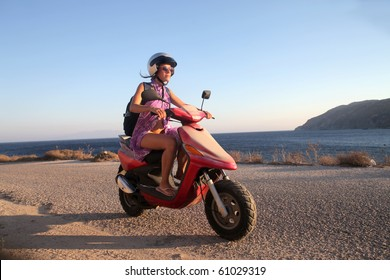 Young woman driving a scooter at the beach