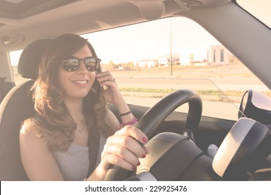 Young woman driving at sunset whit a mobile phone. Filtered picture with vintage effects.