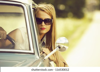 Young woman driving vintage car.