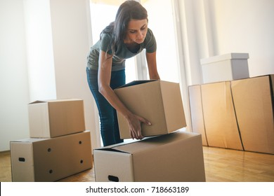 Young woman dropping cardboard box. Moving into a new home