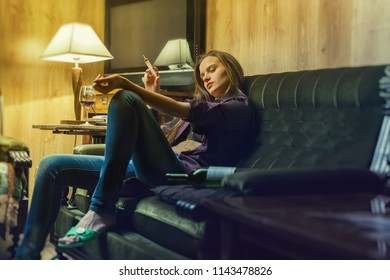 Young woman a drug addict with a syringe in action on the couch in her office