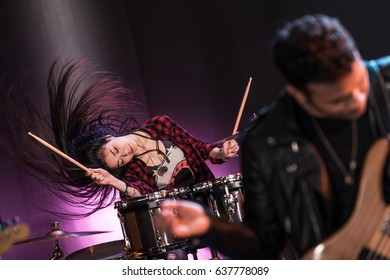 Young woman with drums set playing hard rock music on stage