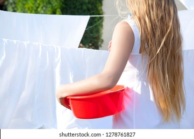 Young woman drying clean laundry in rope outdoors. Girl teenager with basin in hands. Blonde in white dress, rear view