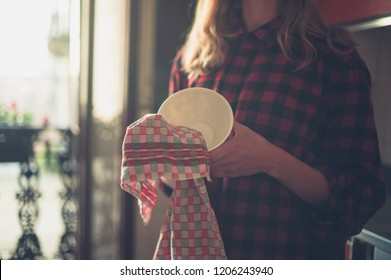 A young woman is drying the dishes in her kitchen