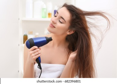 Young woman drying hair after shower in light bathroom at home