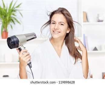 Young woman drying hair at home