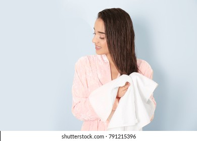 Young woman drying her hair with towel on light background
