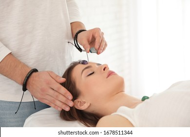 Young woman during crystal healing session in therapy room