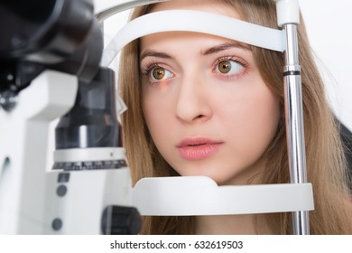 young woman during eyes examination with phoropter at optometric clinic