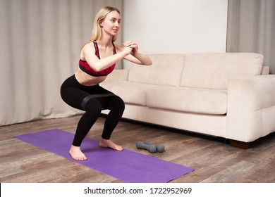 Young woman during her fitness workout at home with rubber resistance band
