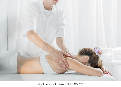 Young woman during relaxing massage in beauty salon