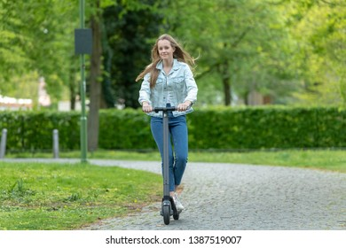 Young woman with e scooter in park