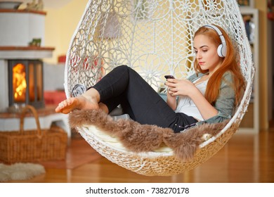 Young woman with earphone relaxing in a hanging chair at home