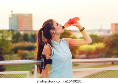 Young woman with Earphones resting and drinking from a plastic bottle after running. Cityscape background. Fitness and workout wellness concept.