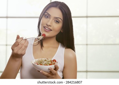 Young woman eating bean sprouts and cherry tomatoes against glass window