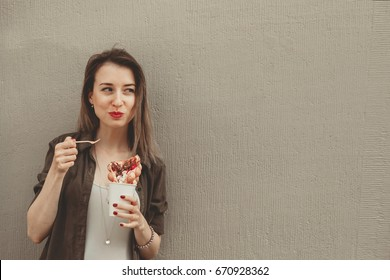 Young woman eating bubble waffle with fruits, chocolate and marshmallow, with copy space.