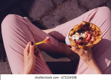Young woman eating bubble waffle with fruits, chocolate and marshmallow, top view.