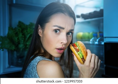 Young woman eating burger from fridge at night kitchen. Diet fail concept
