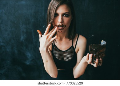 Young woman eating a chocolate cake on a black background. Girl stained with chocolate
