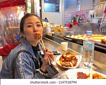 Young woman eating crunchy korean fried chicken street food in Seoul, South Korea