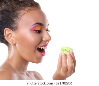 Young woman eating delicious macaroon on white background