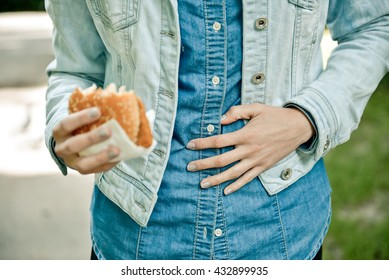 Young woman eating fast food outdoor and feels very bad, she has stomach pain
