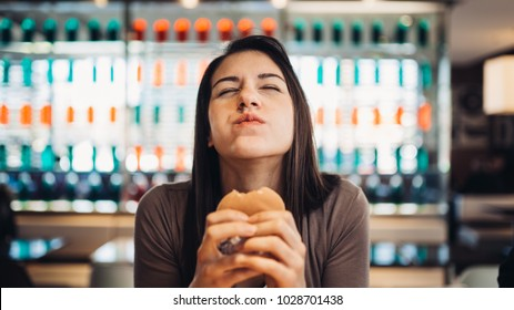 Young woman eating fatty hamburger.Craving fast food.Enjoying guilty pleasure,eating junk food.Satisfied expression.Breaking diet rules,giving up diet.Unhealthy imbalanced nutrition calorie intake.