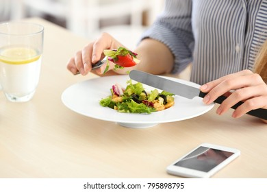 Young woman eating fresh salad at table