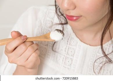 Young woman eating Greek yogurt with chia seeds