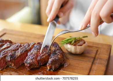 Young woman eating grilled steak in restaurant