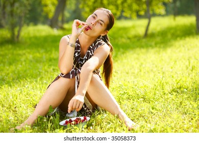A young woman eating a handful of cherries outdoors